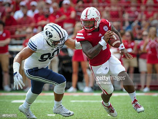 Quarterback Tommy Armstrong Jr #4 of the Nebraska Cornhuskers slips past defensive lineman Bronson Kaufusi of the Brigham Young Cougars during their...