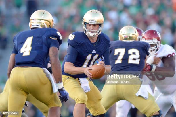 Quarterback Tommy Rees of the Notre Dame Fighting Irish hands the ball off to running back George Atkinson III against the Oklahoma Sooners on...