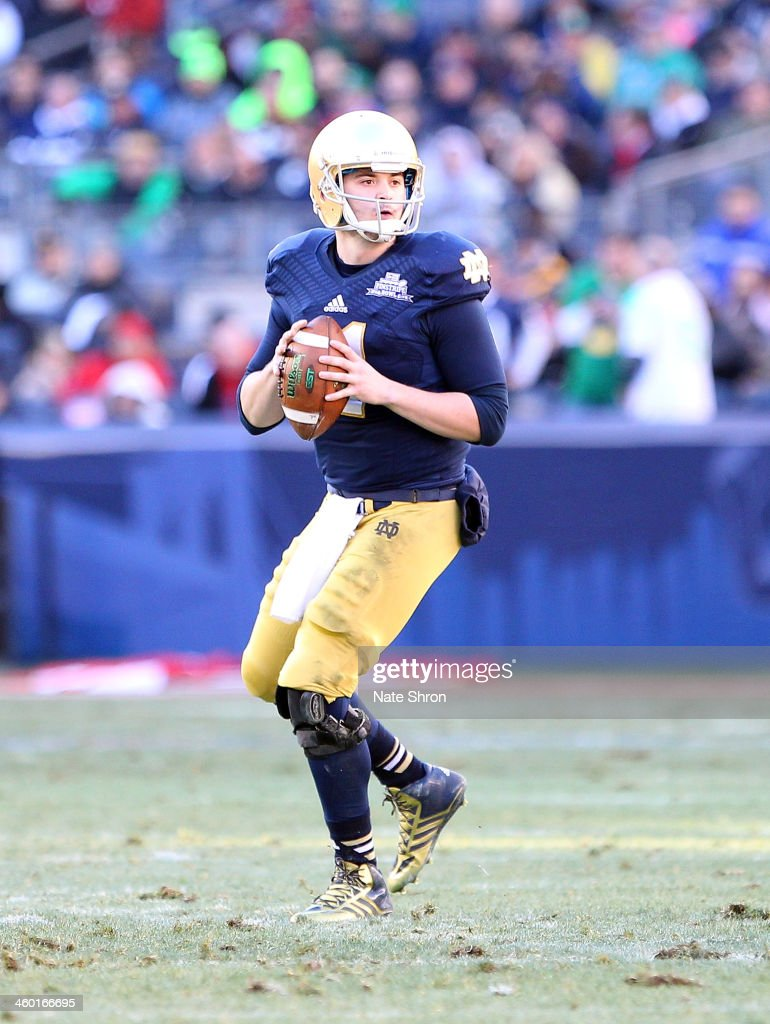 Quarterback Tommy Rees #11 of the Notre Dame Fighting Irish prepares to throw the ball during the game against the Rutgers Scarlet Knights during the New Era Pinstripe Bowl at Yankee Stadium on December 28, 2013 in the Bronx Borough of New York City.