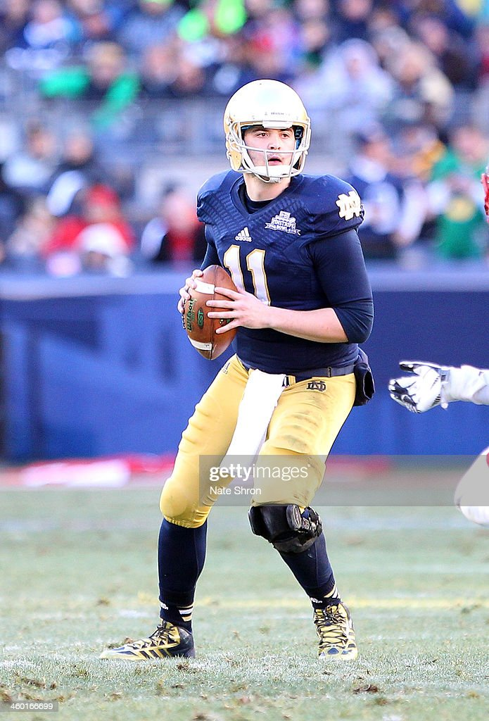 Quarterback <a gi-track='captionPersonalityLinkClicked' href=/galleries/search?phrase=Tommy+Rees+-+American+Football+Player&family=editorial&specificpeople=7175395 ng-click='$event.stopPropagation()'>Tommy Rees</a> #11 of the Notre Dame Fighting Irish prepares to throw the ball during the game against the Rutgers Scarlet Knights during the New Era Pinstripe Bowl at Yankee Stadium on December 28, 2013 in the Bronx Borough of New York City.