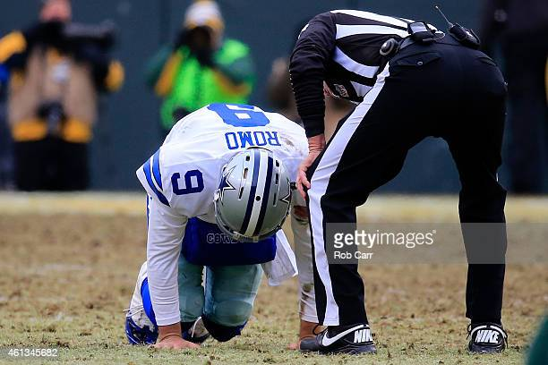 Quarterback Tony Romo of the Dallas Cowboys is slow to get up after being tackled in the third quarter of the 2015 NFC Divisional Playoff game...