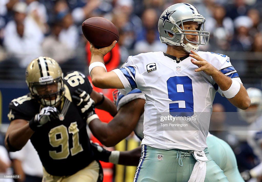 Quarterback <a gi-track='captionPersonalityLinkClicked' href=/galleries/search?phrase=Tony+Romo&family=editorial&specificpeople=756503 ng-click='$event.stopPropagation()'>Tony Romo</a> #9 of the Dallas Cowboys looks for an open receiver under pressure from defensive end <a gi-track='captionPersonalityLinkClicked' href=/galleries/search?phrase=Will+Smith+-+American+Football+Player+-+Born+1981&family=editorial&specificpeople=7237708 ng-click='$event.stopPropagation()'>Will Smith</a> #91 of the New Orleans Saints at Cowboys Stadium on December 23, 2012 in Arlington, Texas. The New Orleans Saints beat the Dallas Cowboys 34-31 in overtime.