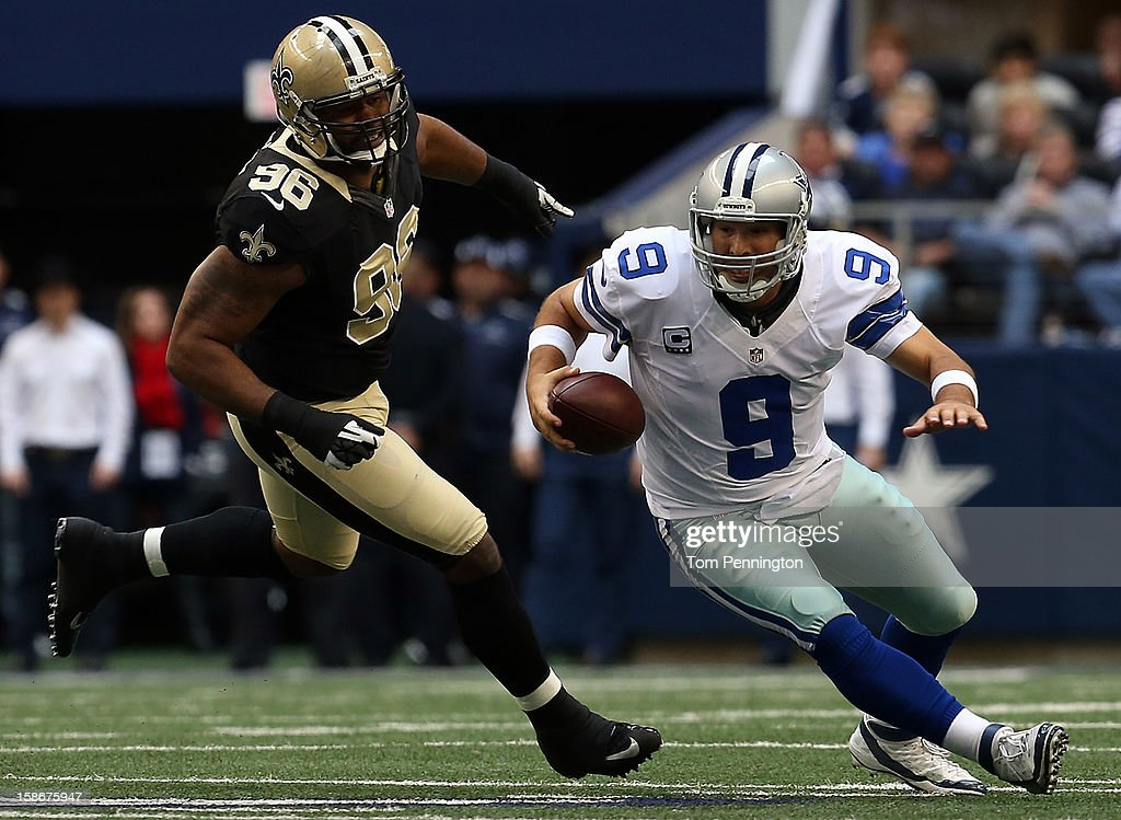 Quarterback Tony Romo #9 of the Dallas Cowboys scrambles with the ball against defensive tackle Tom Johnson #96 of the New Orleans Saints at Cowboys Stadium on December 23, 2012 in Arlington, Texas.