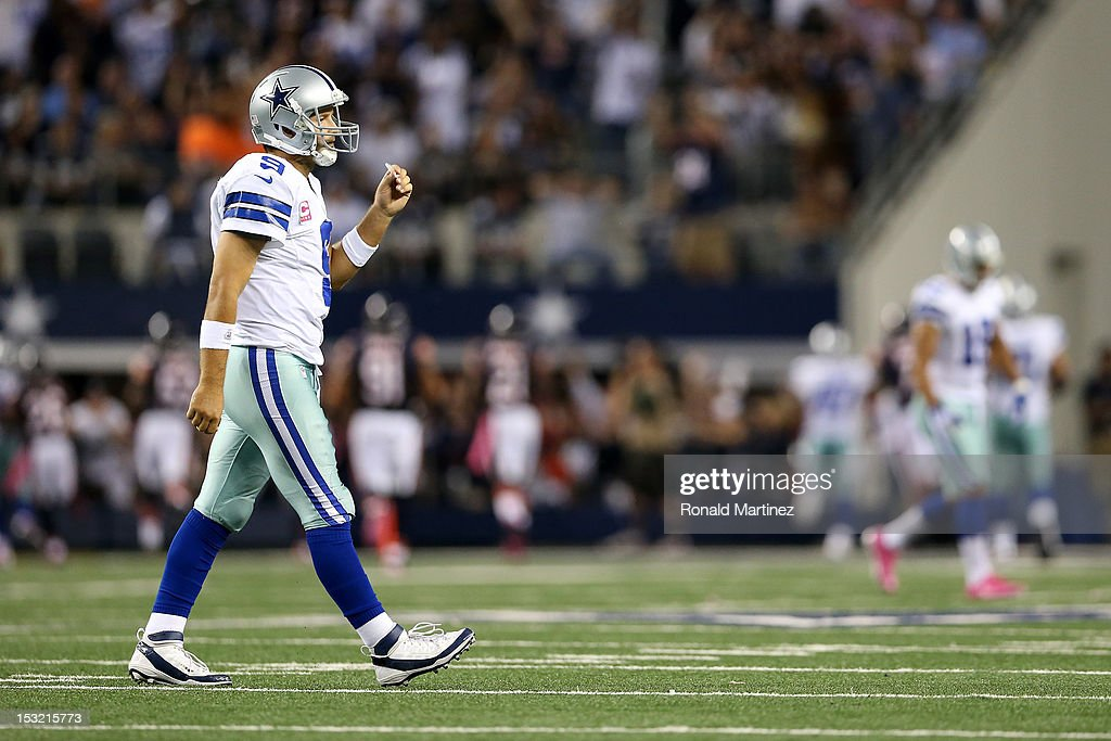 Quarterback <a gi-track='captionPersonalityLinkClicked' href=/galleries/search?phrase=Tony+Romo&family=editorial&specificpeople=756503 ng-click='$event.stopPropagation()'>Tony Romo</a> #9 of the Dallas Cowboys walks towards the sideline after he threw an interception which Lance Briggs #55 of the Chicago Bears returned 74-yards for a touchdown in the third quarter at Cowboys Stadium on October 1, 2012 in Arlington, Texas.