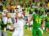 Quarterback Travis Wilson of the Utah Utes celebrates a touchdown as linebacker Danny Mattingly of the Oregon Ducks looks on in the third quarter...