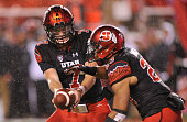 Quarterback Travis Wilson of the Utah Utes hands off to Devontae Booker of the Utah Utes during their game against the Arizona State Sun Devils at...