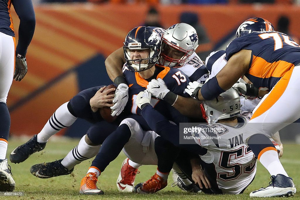 Quarterback Trevor Siemian #13 of the Denver Broncos is sacked by defensive end Trey Flowers #98 of the New England Patriots in the fourth quarter at Sports Authority Field at Mile High on December 18, 2016 in Denver, Colorado.