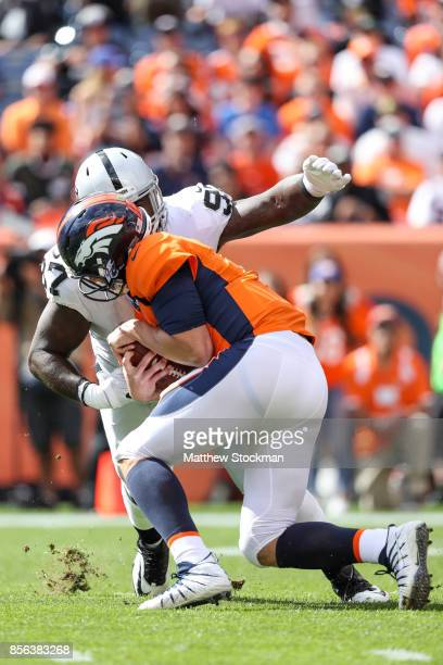 Quarterback Trevor Siemian of the Denver Broncos is sacked by defensive end Mario Edwards of the Oakland Raiders in the first quarter of a game at...