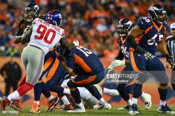 Quarterback Trevor Siemian of the Denver Broncos is sacked by defensive end Jason PierrePaul of the New York Giants in the third quarter of a game at...