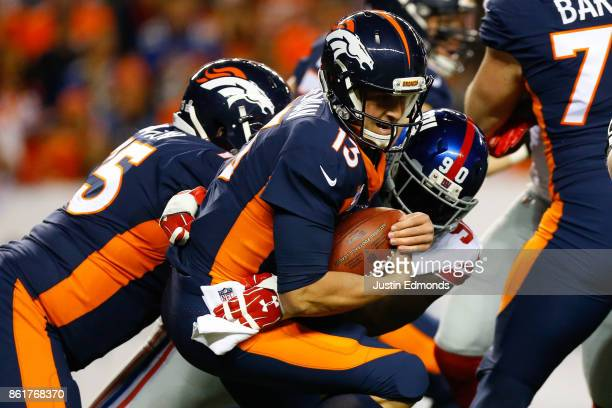 Quarterback Trevor Siemian of the Denver Broncos is tackled by defensive end Jason PierrePaul of the New York Giants after recovering a fumble during...