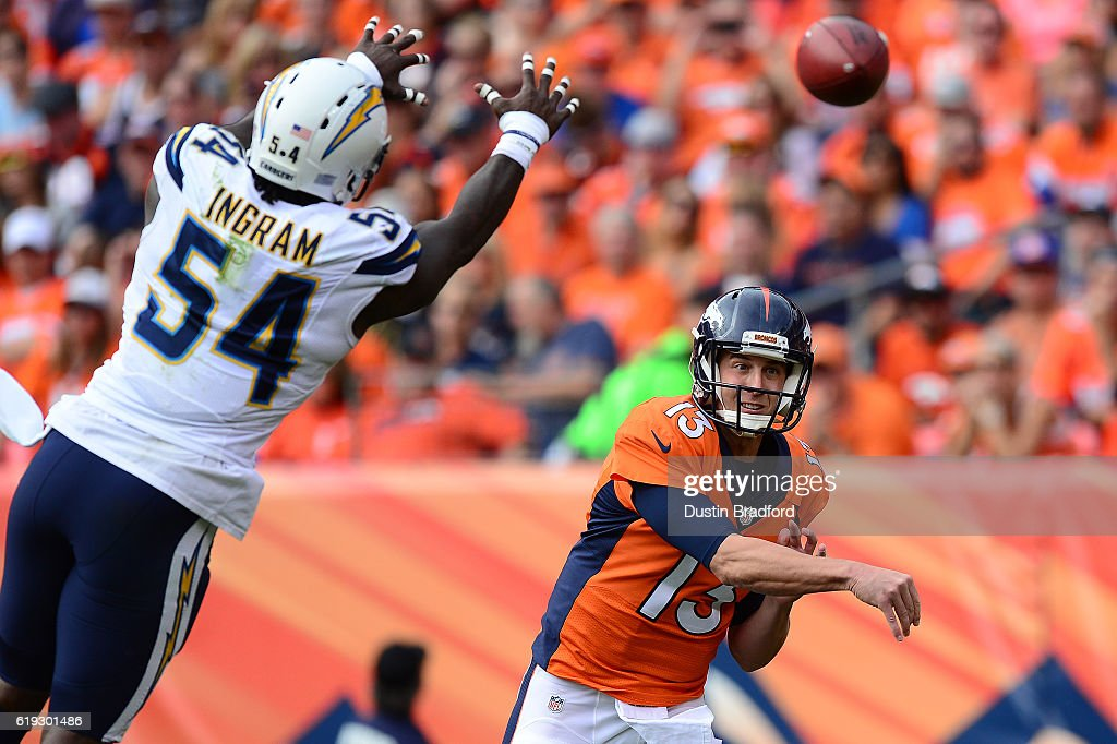 Quarterback Trevor Siemian #13 of the Denver Broncos throws a pass while outside linebacker Melvin Ingram #54 of the San Diego Chargers tries to block it down in the second quarter of the game at Sports Authority Field at Mile High on October 30, 2016 in Denver, Colorado.