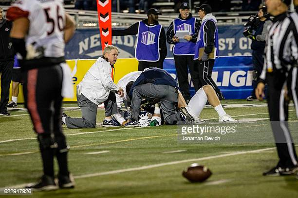 Quarterback Ty Gangi of Nevada lays on the field as head coach Brian Polian looks on after a tackle by San Diego at Mackay Stadium on November 12...