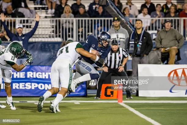Quarterback Ty Gangi of the Nevada Wolf Pack runs to complete a touchdown as linebacker Jahlani Tavai of the Hawaii Rainbow Warriors tries to tackle...