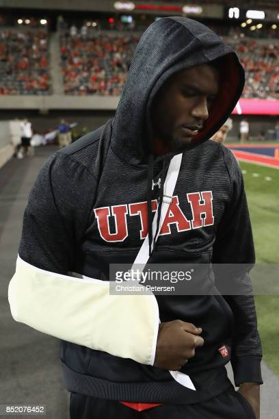 Quarterback Tyler Huntley of the Utah Utes walks back onto the field in street clothes after an injury during the second half of the college football...