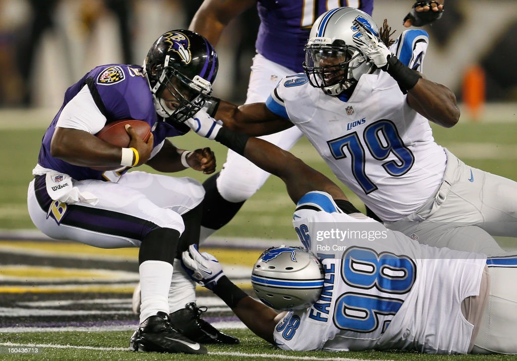 Quarterback Tyrod Taylor #2 of the Baltimore Ravens is sacked by Nick Fairley #98 and Willie Young #79 of the Detroit Lions during the second quarter at M&T Bank Stadium on August 17, 2012 in Baltimore, Maryland.