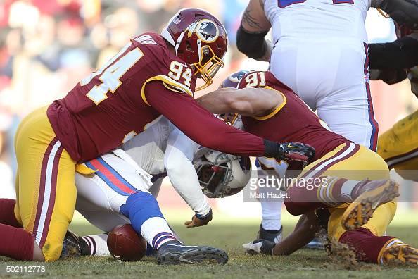 Quarterback Tyrod Taylor of the Buffalo Bills is sacked by linebacker Preston Smith and outside linebacker Ryan Kerrigan of the Washington Redskins...