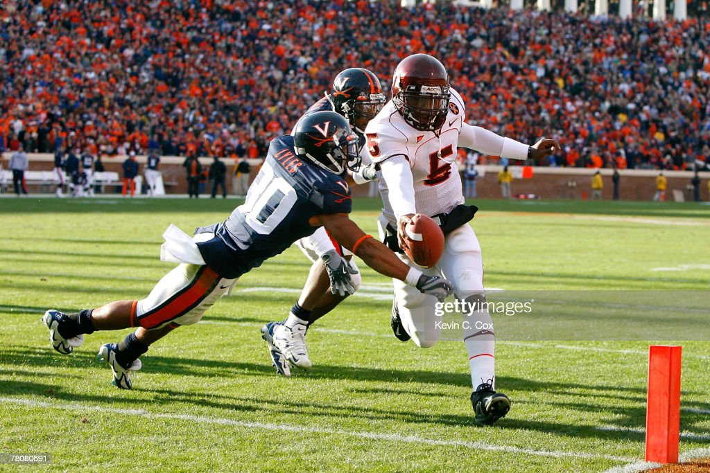 Quarterback Tyrod Taylor of the Virginia Tech Hokies scores a touchdown against defenders Nate Lyles and Jermaine Dias of the Virginia Cavaliers...