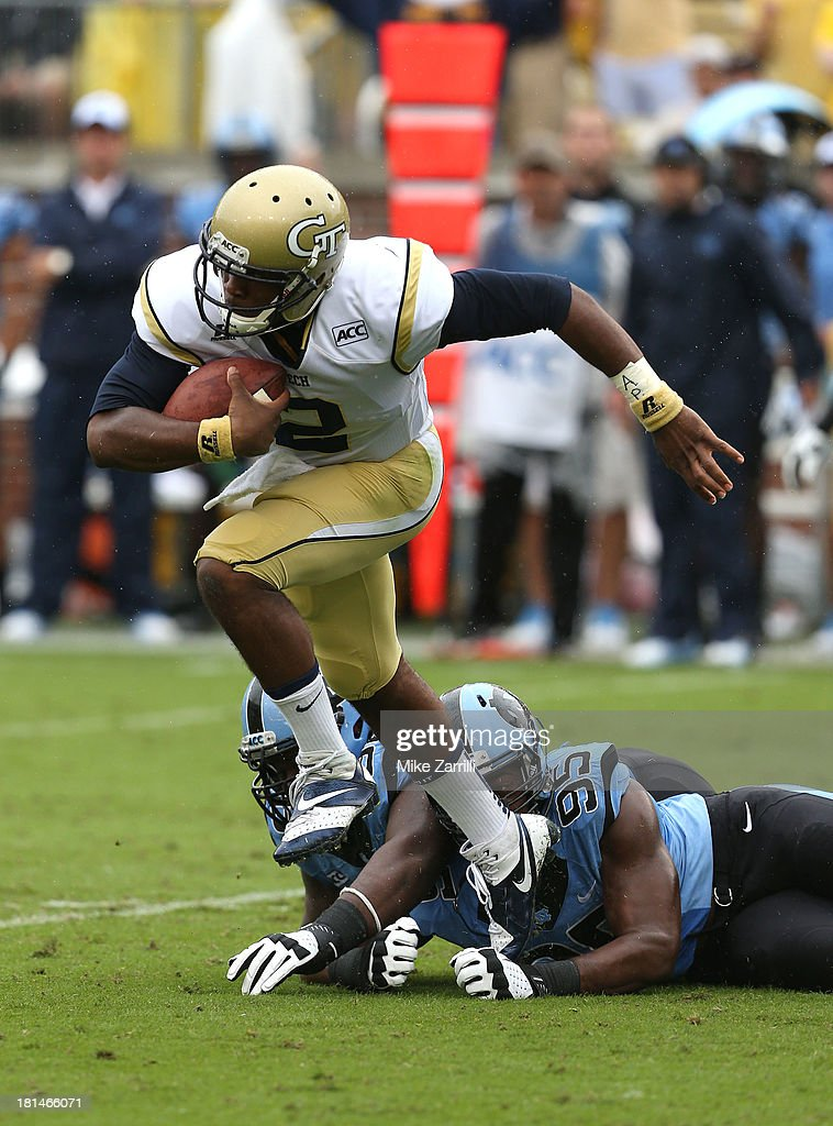 Quarterback Vad Lee #2 of the Georgia Tech Yellow Jackets breaks away from defensive tackle Justin Thomason of the North Carolina Tar Heels during the game at Bobby Dodd Stadium at Historic Grant Field on September 21, 2013 in Atlanta, Georgia.