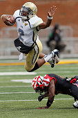 Quarterback Vad Lee of the Georgia Tech Yellow Jackets jumps over defensive back Jeremiah Johnson of the Maryland Terrapins during the second half of...