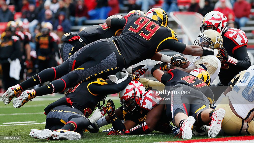 Quarterback Vad Lee #2 of the Georgia Tech Yellow Jackets scores a second half touchdown as defensive lineman Quinton Jefferson #99 of the Maryland Terrapins tries to stop him during the Yellow Jackets 33-13 win at Byrd Stadium on November 3, 2012 in College Park, Maryland.