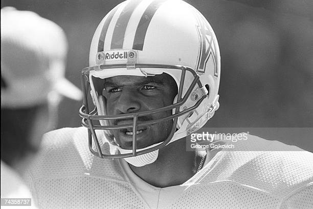 Quarterback Warren Moon of the Houston Oilers talks with coaches on the sideline during a game against the Washington Redskins at RFK Stadium on...