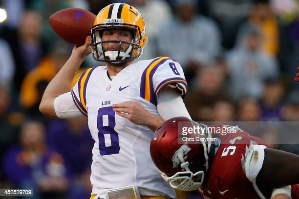 Quarterback Zach Mettenberger of the LSU Tigers throws a pass as he is hit by Byran Jones of the Arkansas Razorbacks at Tiger Stadium on November 29...