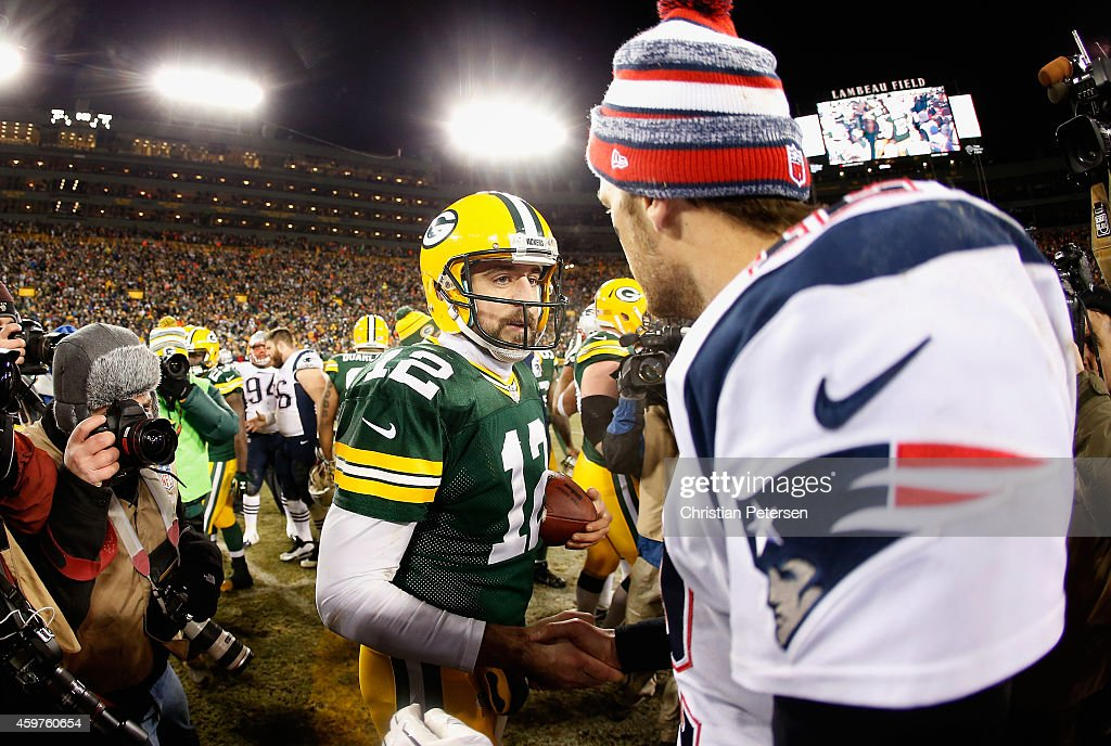 Quarterbacks Aaron Rodgers of the Green Bay Packers and Tom Brady of the New England Patriots shake hands following the NFL game at Lambeau Field on...