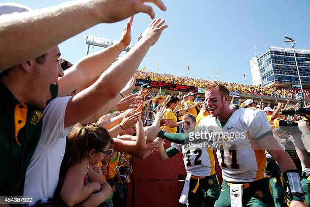 Quarterbacks Carson Wentz and quarterback Easton Stick of the North Dakota State Bison celebrate with fans after defeating the Iowa State Cyclones...
