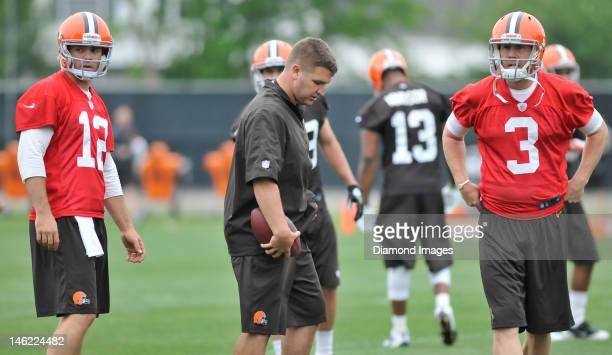 Quarterbacks Colt McCoy and Brandon Weeden the Cleveland Browns stand on the field during an organized team activity practice on May 22 2012 at the...