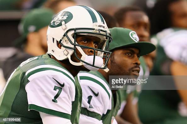 Quarterbacks Geno Smith of the New York Jets and Michael Vick look on from the bench in the fourth quarter against the Buffalo Bills at MetLife...