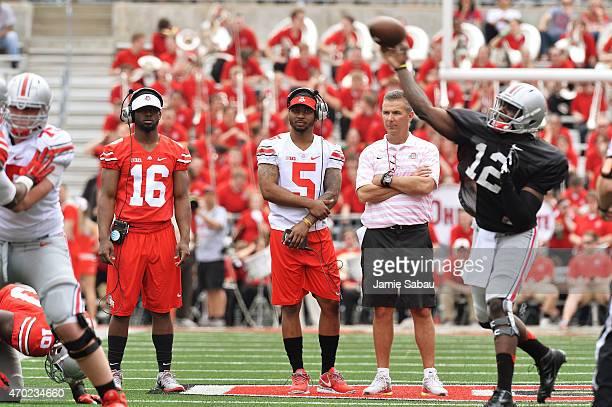 Quarterbacks JT Barrett of the Ohio State Buckeyes and Braxton Miller of the Ohio State Buckeyes watch alongside Head Coach Urban Meyer of the Ohio...