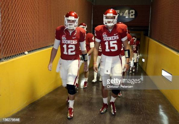 Quarterbacks Landry Jones and Drew Allen of the Oklahoma Sooners walk out onto the field before the Insight Bowl against the Iowa Hawkeyes at Sun...