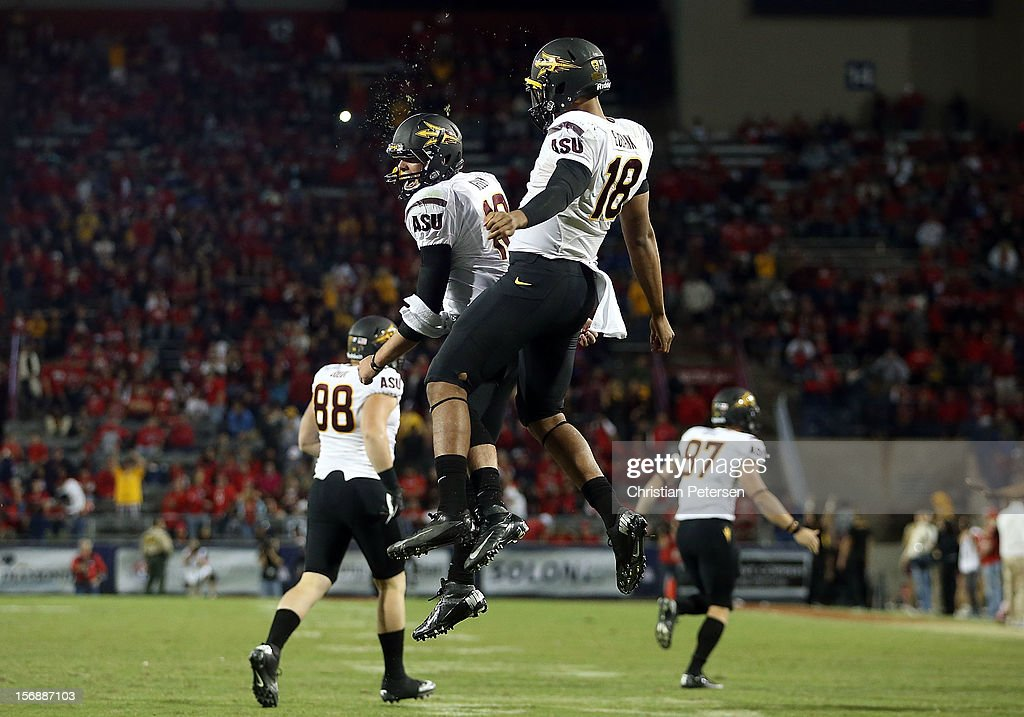 Quarterbacks Michael Eubank #18 and Taylor Kelly #10 of the Arizona State Sun Devils celebrate after Eubank scored a 1 yard rushing touchdown against the Arizona Wildcats during the fourth quarter of the college football game at Arizona Stadium on November 23, 2012 in Tucson, Arizona. The Sun Devils defeated the Wildcats 41-34.