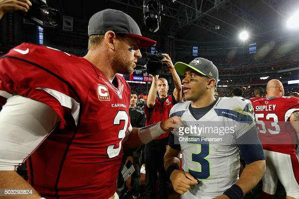 Quarterbacks Russell Wilson of the Seattle Seahawks and Carson Palmer of the Arizona Cardinals talk on the field following the NFL game at the...