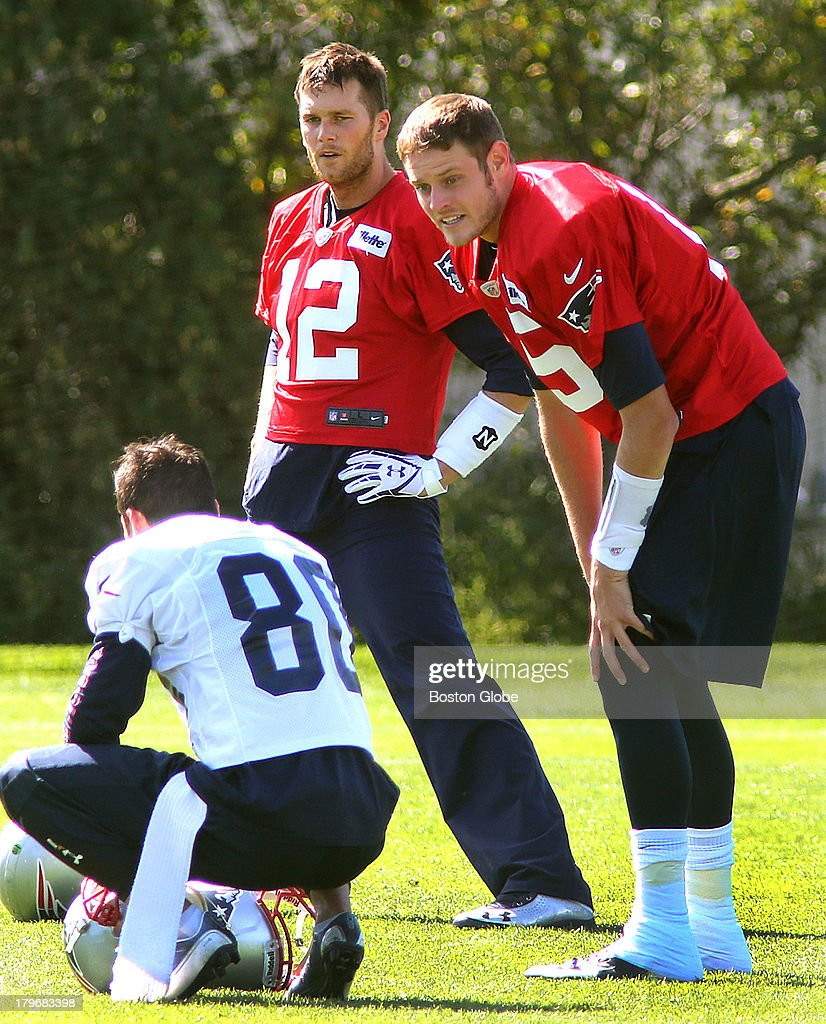 Quarterbacks Tom Brady, left, and Ryan Mallett take a break during stretching as they chat with Danny Amendola. The New England Patriots held practice on the practice fields at Gillette Stadium.