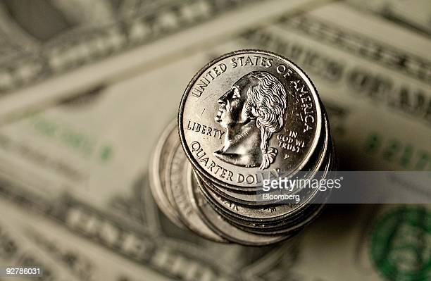 US quarters and US dollar bills are arranged for a photograph in New York US on Tuesday Aug 18 2009 The dollar may fall to a threeweek low against...