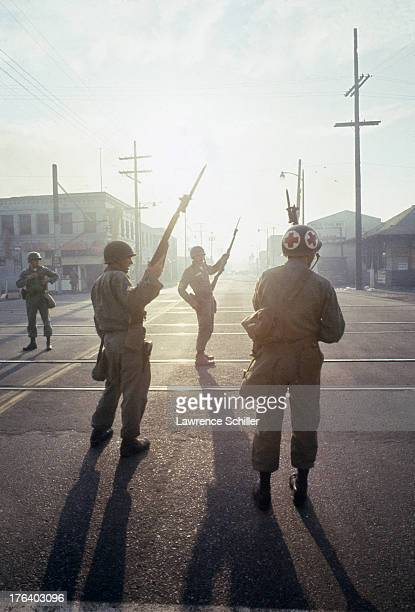 A quartet of National Guardsmen one a medic stand watch in an intersection in the Watts neighborhood after the declaration of Marshall Law due to...