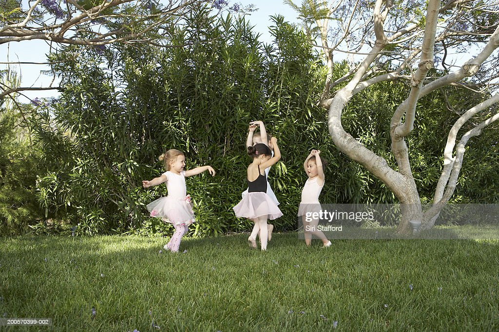 Quartet of young girls (3-4) dressed as ballerinas dancing in park : Stock Photo