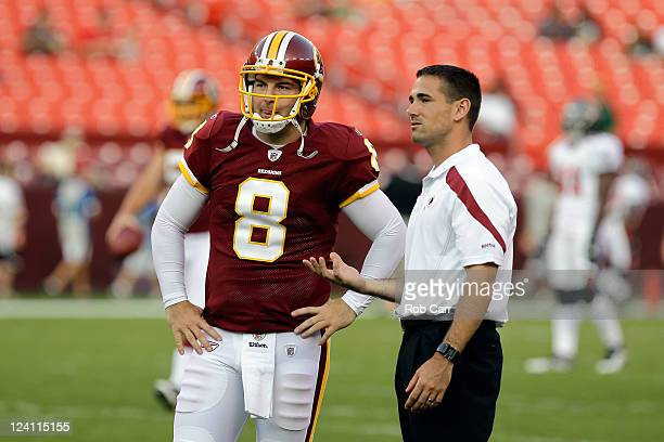 Quartrback Rex Grossman of the Washington Redskins talks with offensive coordinator Kyle Shanahan before the start of a preseason game against the...