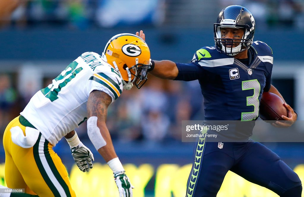 Quaterback Russell Wilson of the Seattle Seahawks escapes the tackle attempt of safety Ha Ha ClintonDix of the Green Bay Packers at CenturyLink Field...
