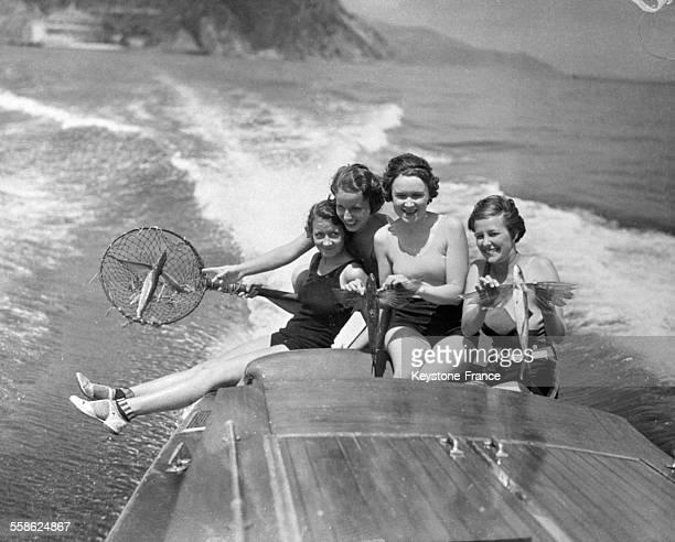 Quatre jeunes filles sur un canot à moteur avec un poisson volant qu'elles viennent d'attraper dans leur filet en Californie EtatsUnis le 30 avril...