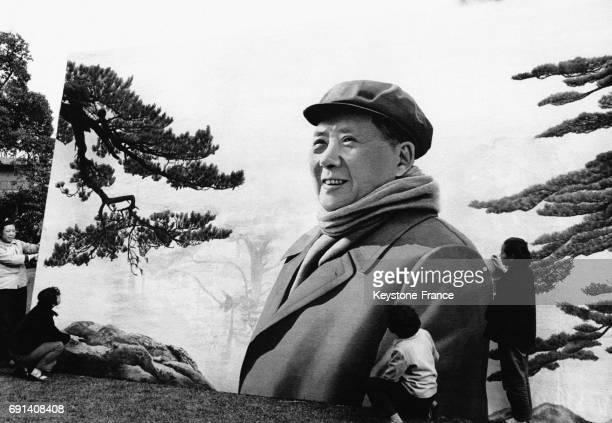 Quatre ouvrières chinoises devant une grande broderie sur soie réalisée par 55 couturières et représentant le dirigeant de la République Populaire de...