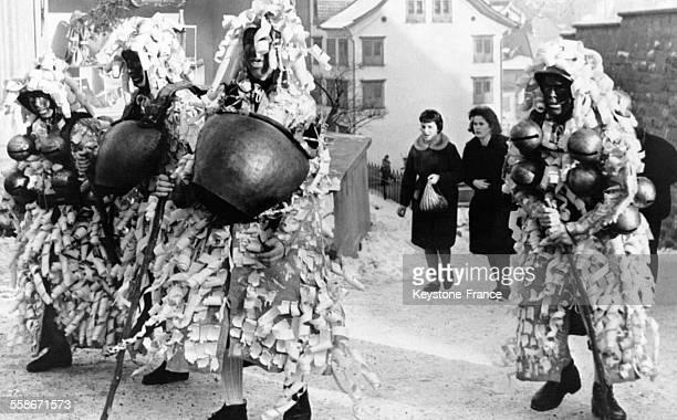 Quatre personnes portant des costumes étranges célèbrent le Nouvel An selon une tradition millénaire en secouant des cloches de vache dans les rues...