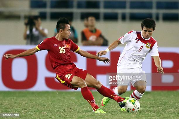 Que Ngoc Hai of Vietnam battles K Lithideth of Laos during the 2014 AFF Suzuki Cup Group A match between Laos and Vietnam at the My Dinh Stadium on...