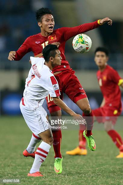 Que Ngoc Hai of Vietnam battles with KSihavong of Laos during the 2014 AFF Suzuki Cup Group A match between Laos and Vietnam at the My Dinh Stadium...