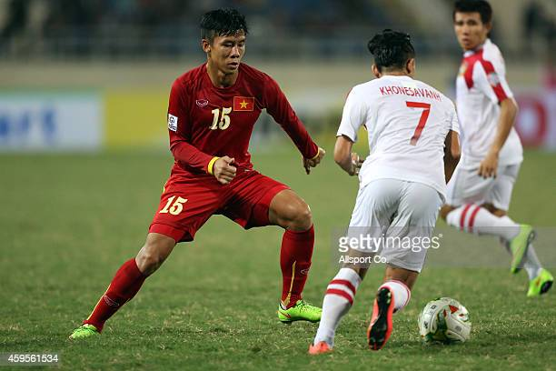 Que Ngoc Hai of Vietnam checks KSihavong of Laos during the 2014 AFF Suzuki Cup Group A match between Laos and Vietnam at the My Dinh Stadium on...