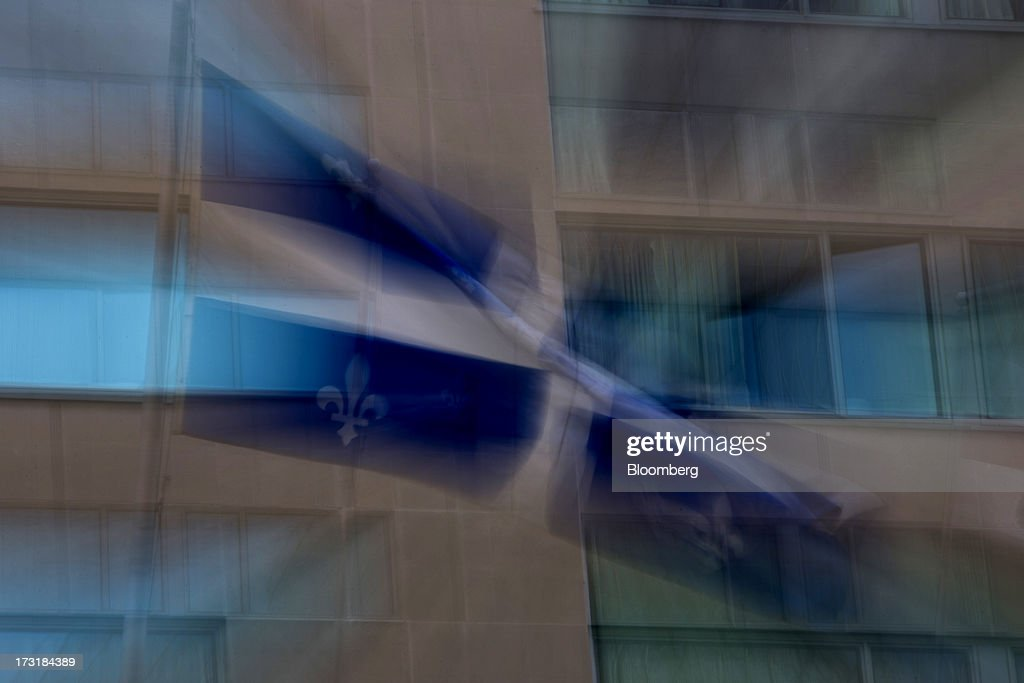 A Quebec flag flies in Montreal, Quebec, Canada, on Monday, July 8, 2013. Montreals city council elected Laurent Blanchard as interim mayor to replace Michael Applebaum, who quit last week after being arrested on corruption charges. Photographer: Brent Lewin/Bloomberg via Getty Images