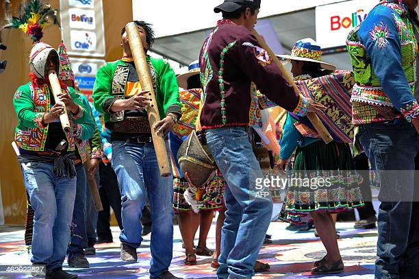 Quechua indigenous people play and dance traditional music as they celebrate the arrival of motorcycles and quads during the 2014 Rally Dakar stage 7...