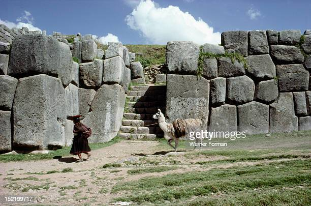 Quechua woman and llama walking past a monumental Inca doorway and wall at Sacsahuaman Sacsahuaman was the great Inca fortress protecting and...