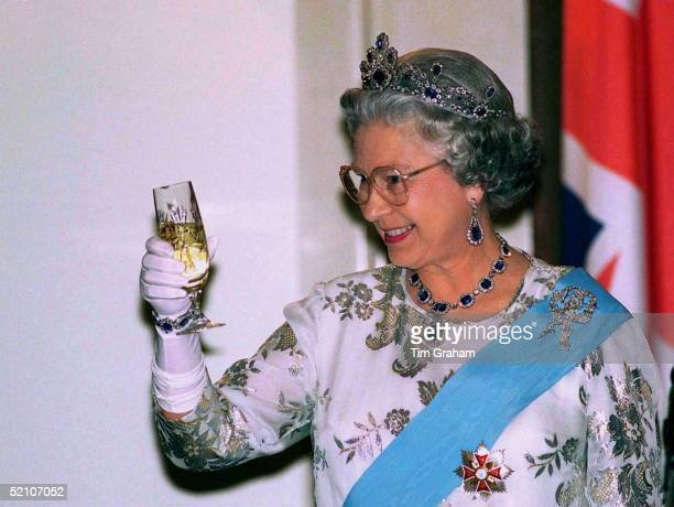 Queen At Banquet At Presidential Palace Toasting Her Host With A Glass Of Champagne In Warsaw During Her Visit To Poland